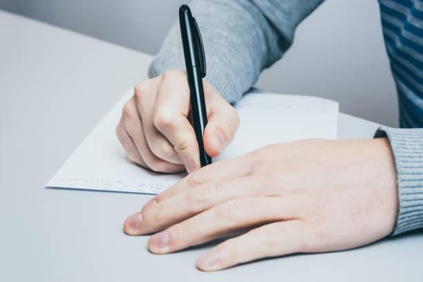 L'homme est assis à la table et écrit avec un stylo sur le papier - Photo