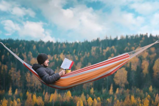 en man sitter i en hängmatta och läser en bok i en pittoresk plats. mugg i högra handen. - norrbotten bildbanksfoton och bilder