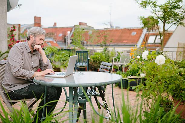 mann sitzt in seinem garten auf der dachterrasse und arbeitet auf laptop - garden types stock-fotos und bilder