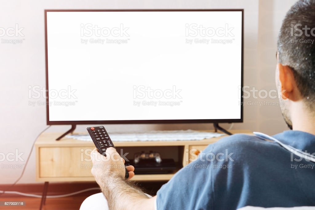 Man sits in sofa watching tv stock photo