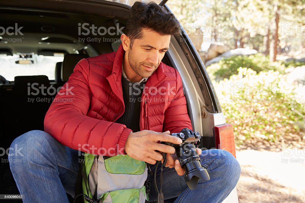 Man sits in the open back of car in forest checking stock photo