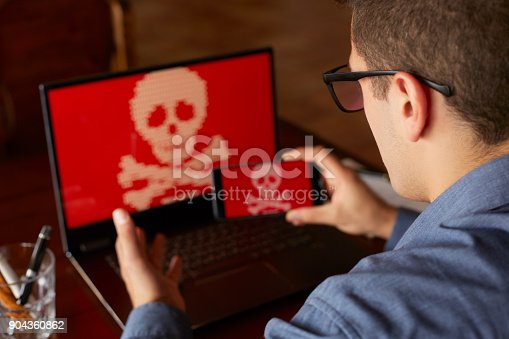 812847754 istock photo Man sits near laptop with phone blocked and encrypted by ransomware spyware asking for money. Laptop and smartphone infected by virus. Scary red skull crossbones on screen. Cyber security concept 904360862