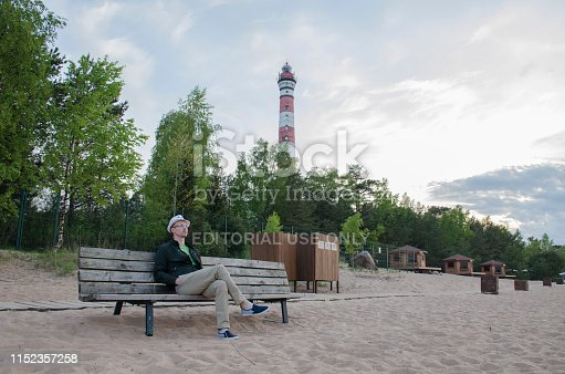 St. Petersburg, Russia - May 20, 2019: Young man with glasses, in light trousers, green jacket and white hat its on a bench on a sandy beach and looks in the evening against the backdrop of trees, lighthouse and sunset sky