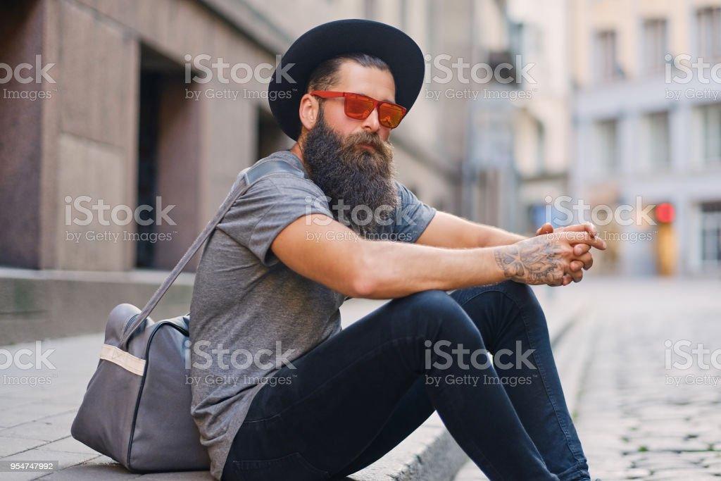 Um homem senta-se em um passo numa rua. - foto de acervo