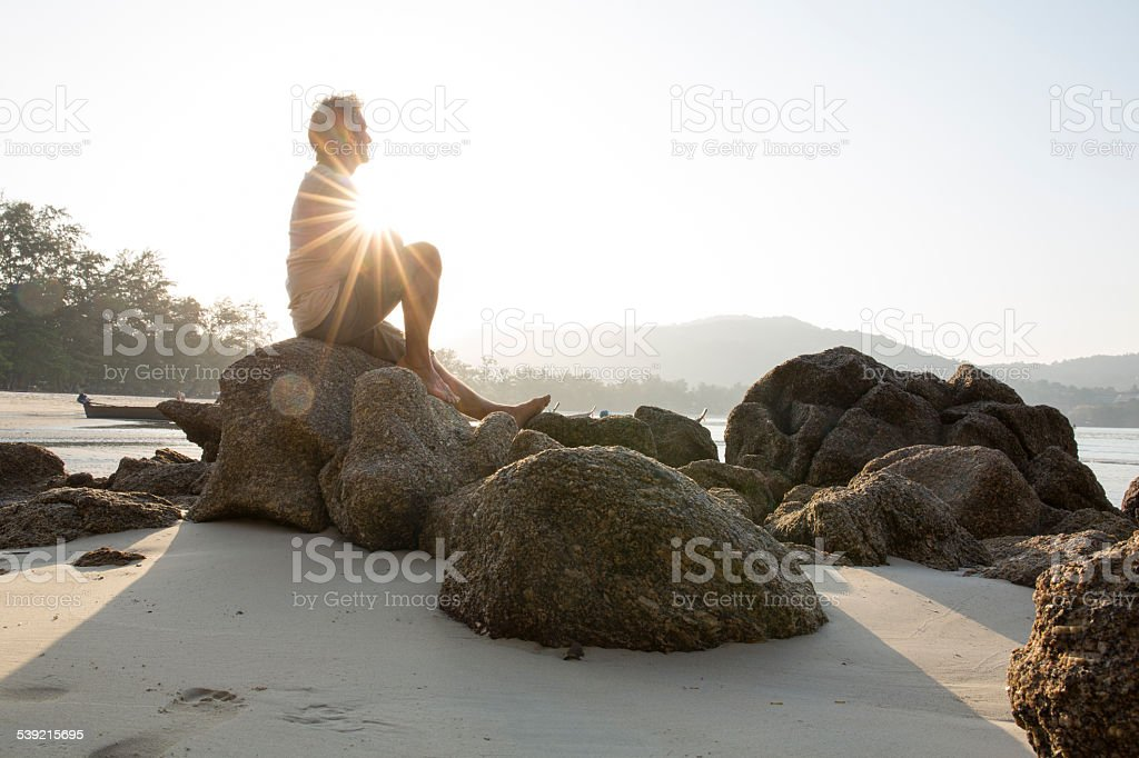 Man sits on beach boulder, looks out to view stock photo