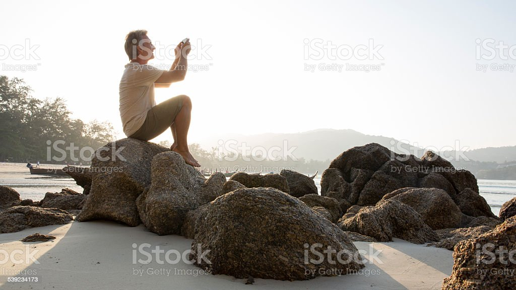 Man sits on beach boulder, takes pic of view royalty-free stock photo