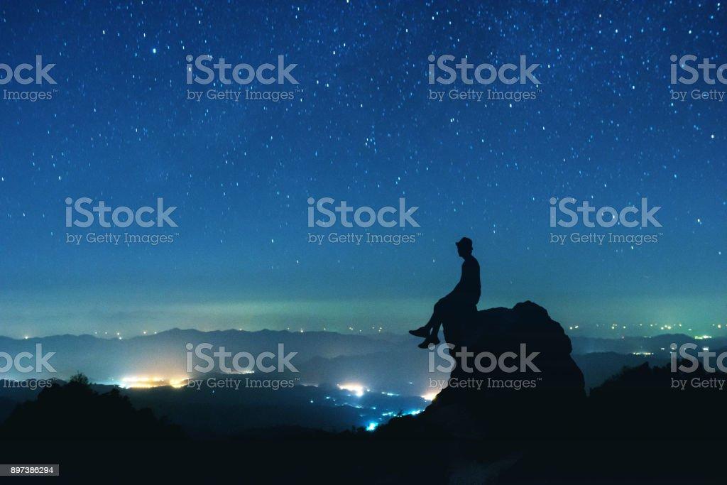 Hombre se sienta sobre la gran roca en el fondo del cielo nocturno - foto de stock