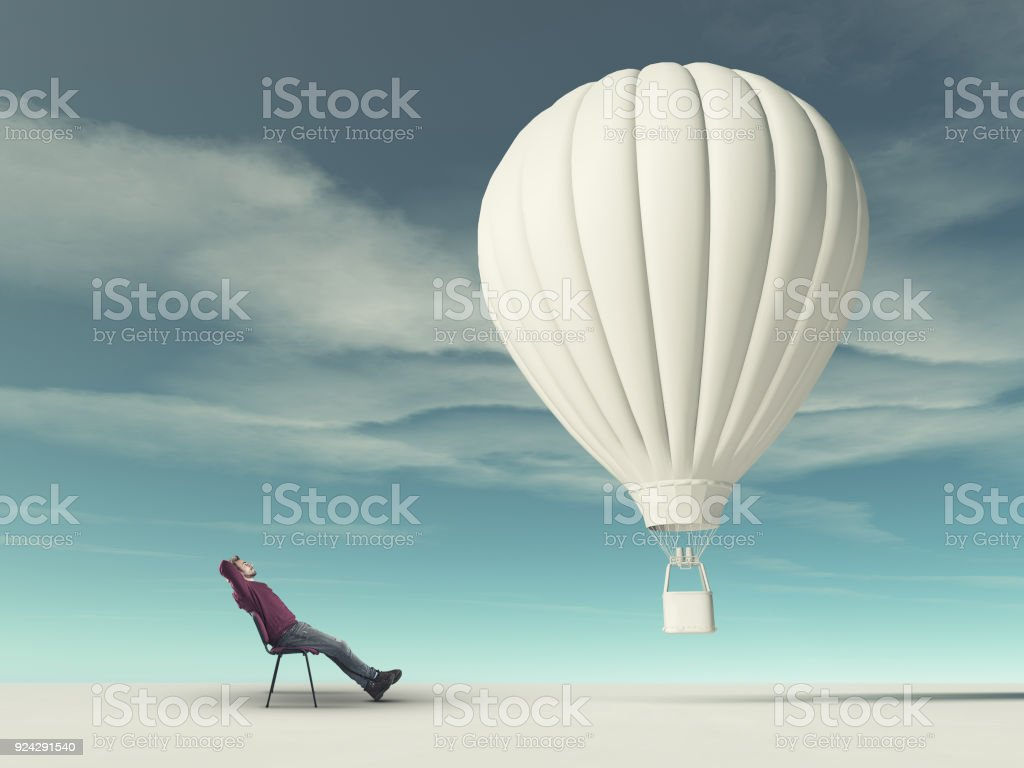 Man sits on chair and looks at a white hot air balloon