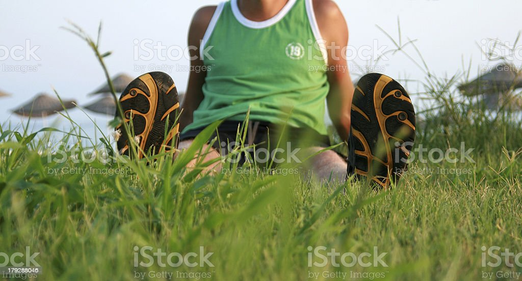 Man sits on grass in summer flip-flops royalty-free stock photo