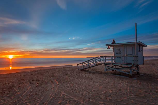 man sits on lifeguard tower at sunset on beach. - badvaktshytt bildbanksfoton och bilder