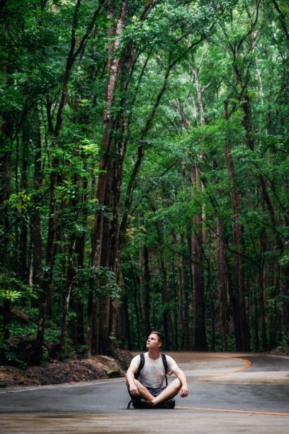 Man sits on road, Bilar Man-Made Forest, Bohol, Philippines stock photo