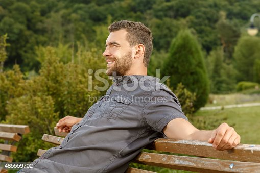 istock Man sits on the bench and relax in public park 485559702