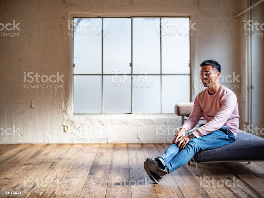 A man sits on the couch in the warm sunshine and relaxes.
