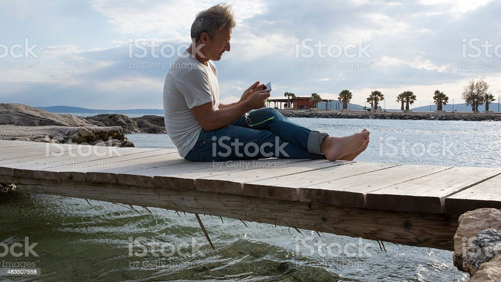 Man sits on wooden bridge above sea,texting stock photo