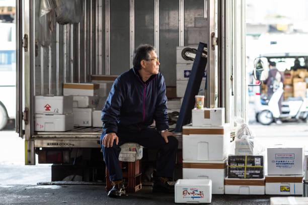 hombre se sienta fuera del delviery carro y esperando nuevas entregas en el mercado de pescado de tsukiji, tokio, japón - pez sierra fotografías e imágenes de stock
