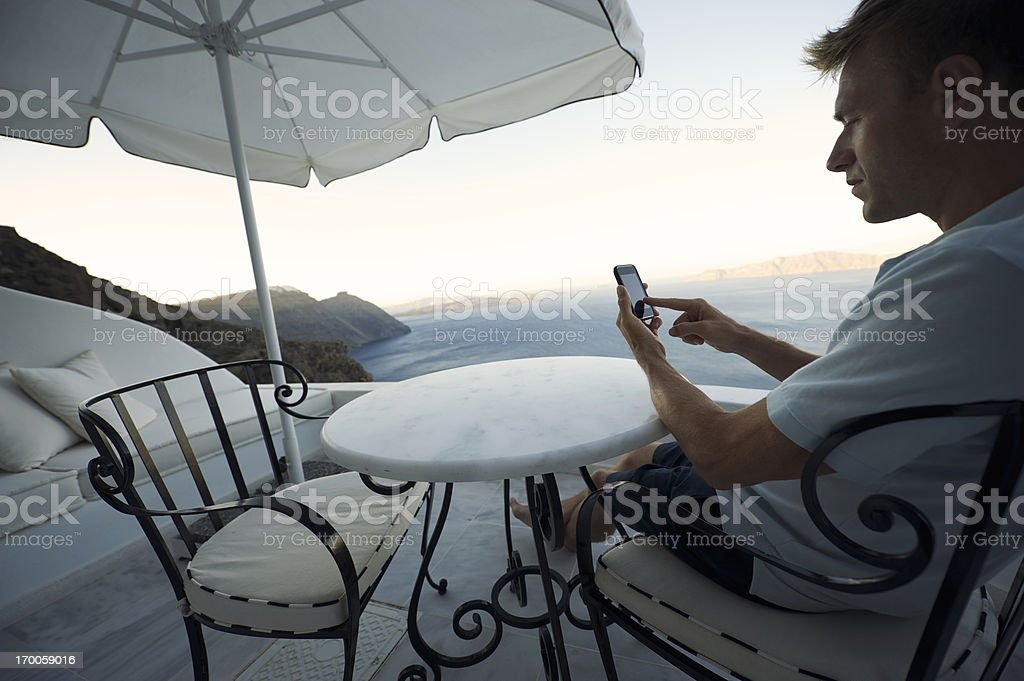 Man Sits Using Smartphone on Santorini Morning Balcony royalty-free stock photo