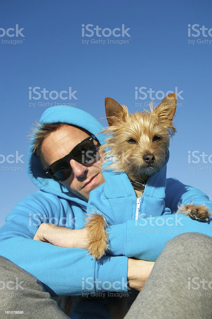 Man Sits with Dog in Matching Blue Hoody Sweatshirts stock photo