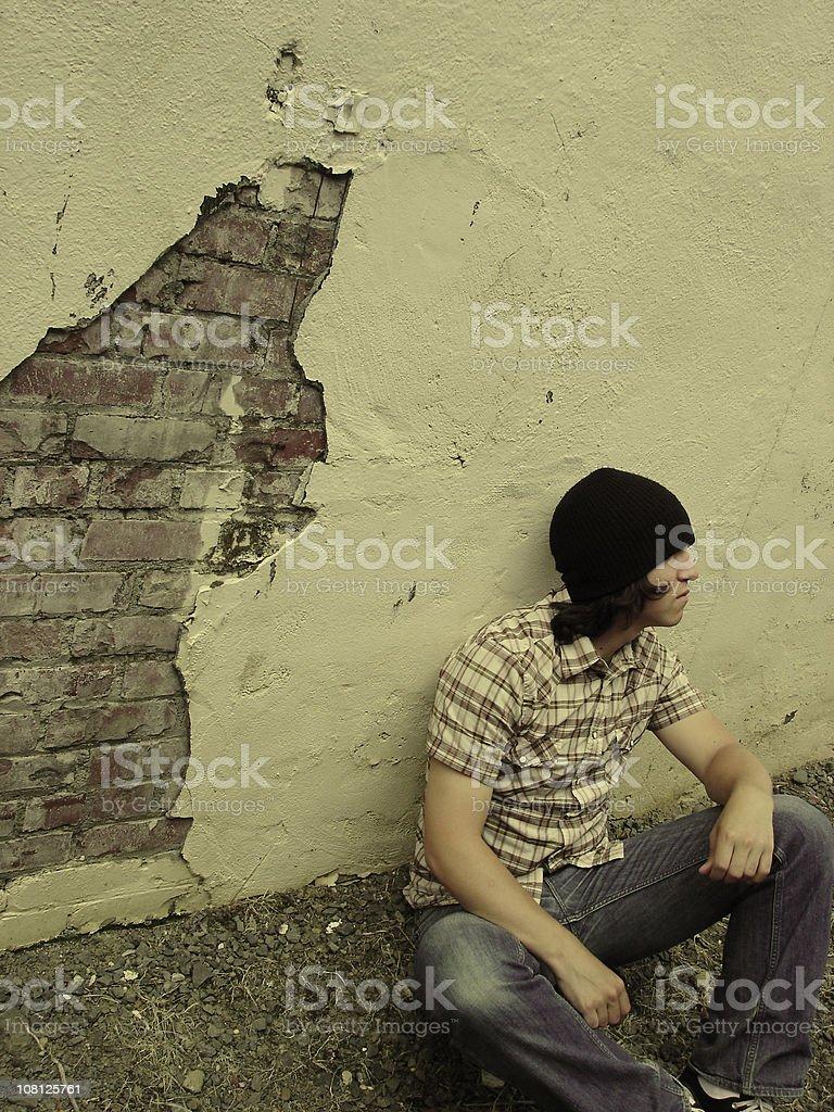 Man Sitting Against Brick Wall royalty-free stock photo