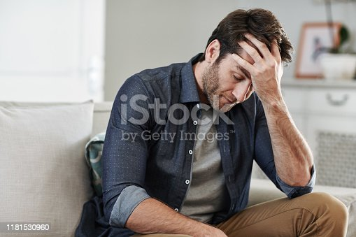 Man looking depressed while sitting alone with his head in his hand on his living room sofa at home