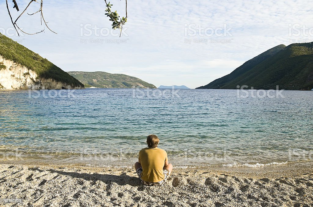 Man sitting alone on beach royalty-free stock photo