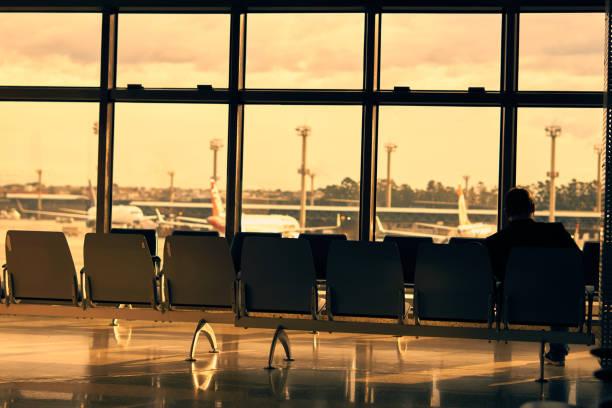 Mann sitzt allein auf der Bank in der Lobby von Guarulhos International Airport. – Foto