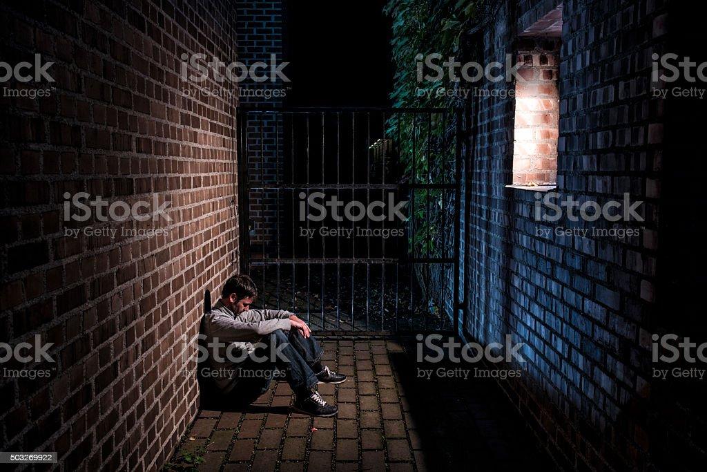Man Sitting Alone Outside At Night Below Window Royalty Free Stock Photo
