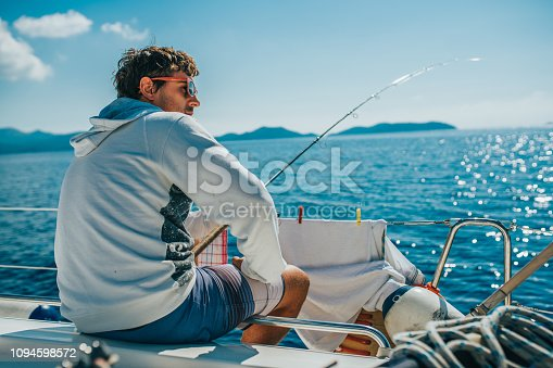 Man sitting and fishing on boat