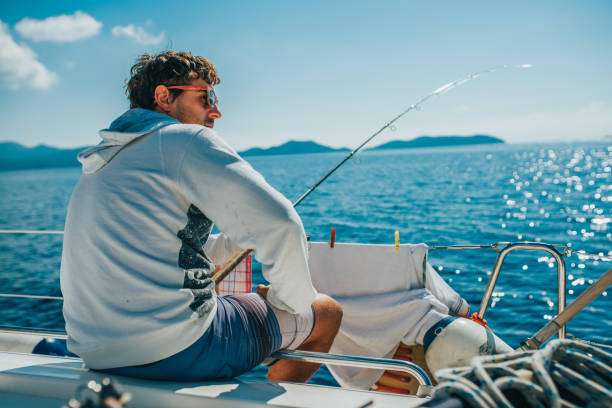 Man sitting and fishing on boat stock photo