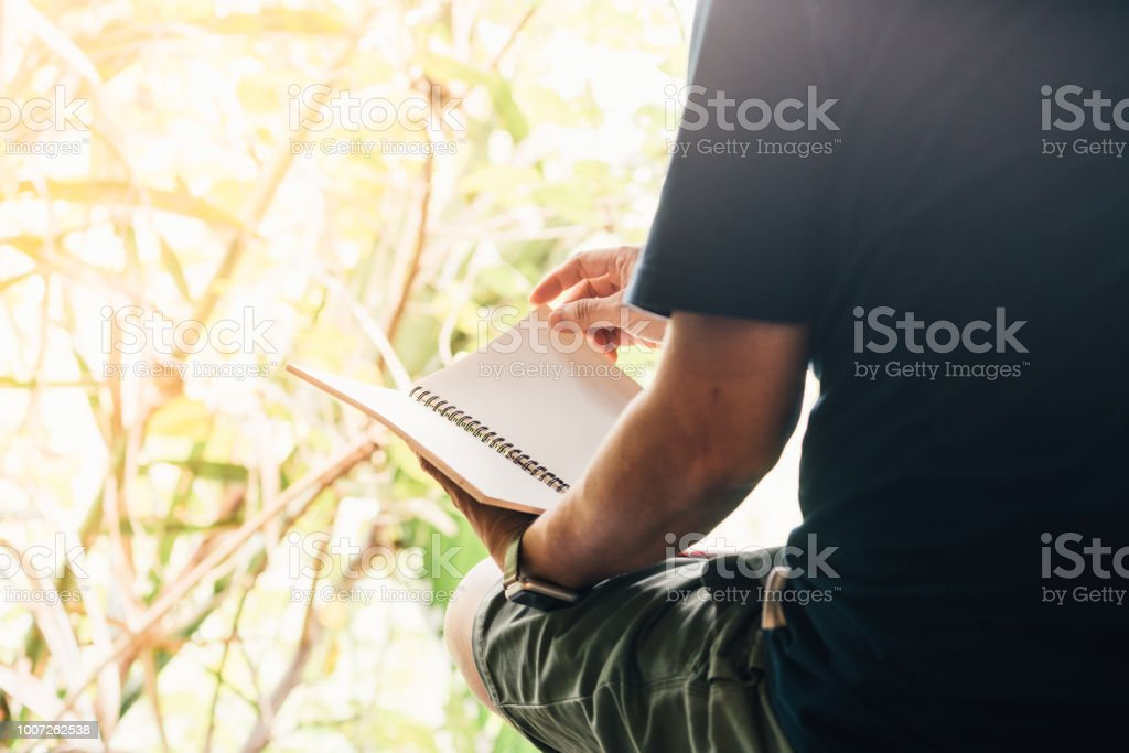 Man sitting and holding and reading book outdoor with green nature...