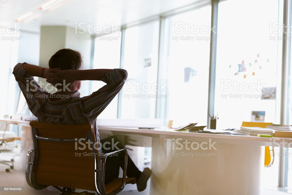 Man sitting arms behind head relaxed in office meeting room