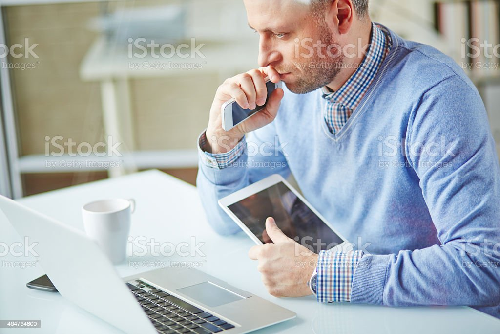 Man sitting at a computer desk with a tablet and smartphone stock photo