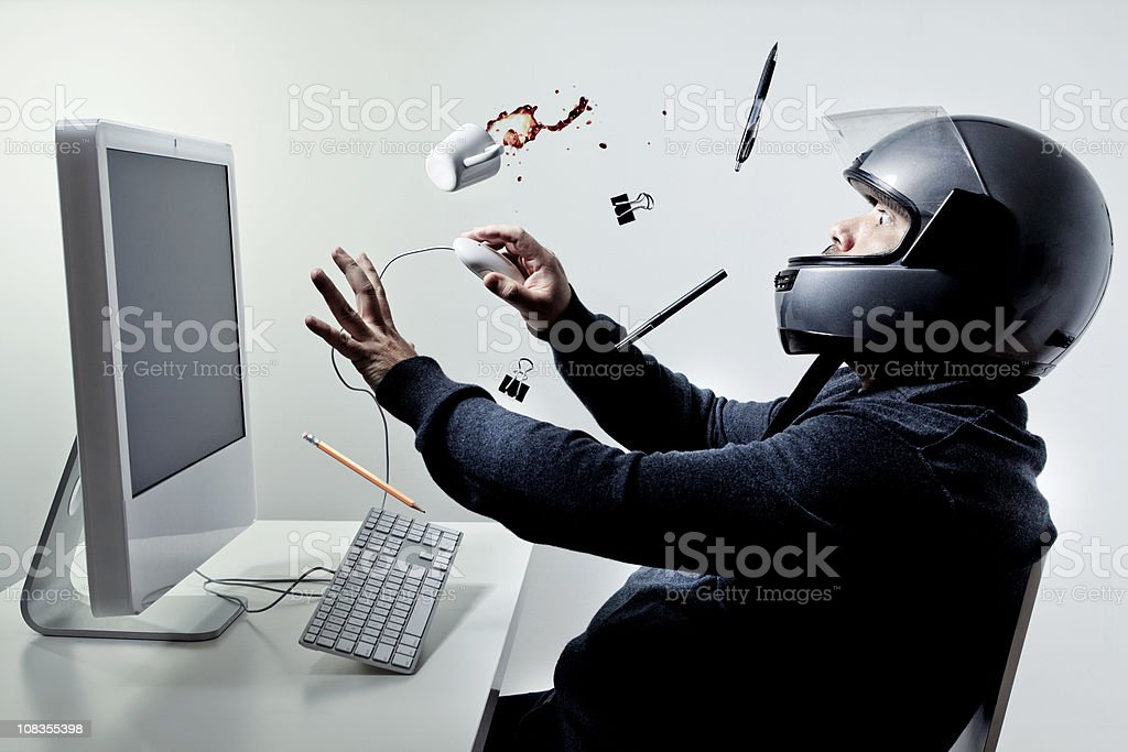 Man sitting at a computer wearing motorcycle helmet stock photo