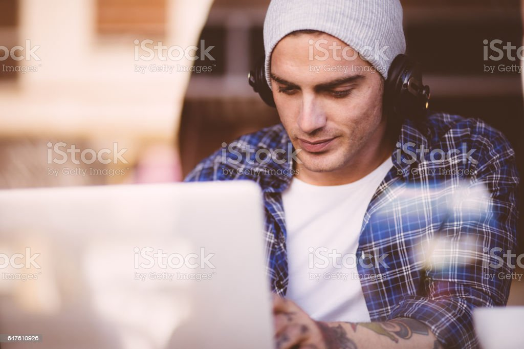 Man sitting at  cafe window with a laptop and headphones stock photo
