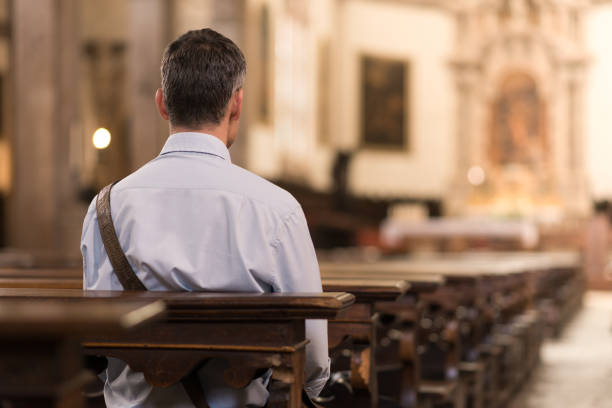 Man sitting at Church Man sitting in a pew at Church and meditating, faith and religion concept pew stock pictures, royalty-free photos & images