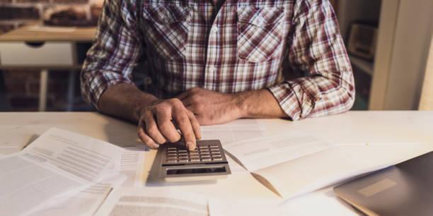 Mann am Schreibtisch sitzt und seine inländischen Rechnungsprüfung, benutzt er einen Taschenrechner, Eigenheim-Finanzierung-Konzept – Foto