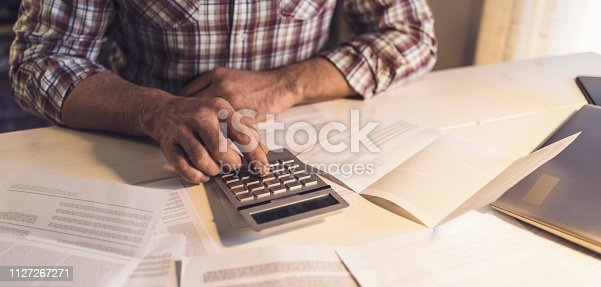 istock Man sitting at desk and checking his domestic bill, he is using a calculator, home finance concept 1127267271