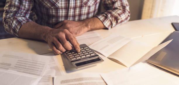 O homem sentado na mesa e verificando a sua lei nacional, ele está usando uma calculadora, o conceito de finanças em casa - foto de acervo