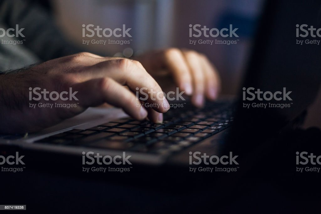 Man sitting at desk and working on laptop at night stock photo