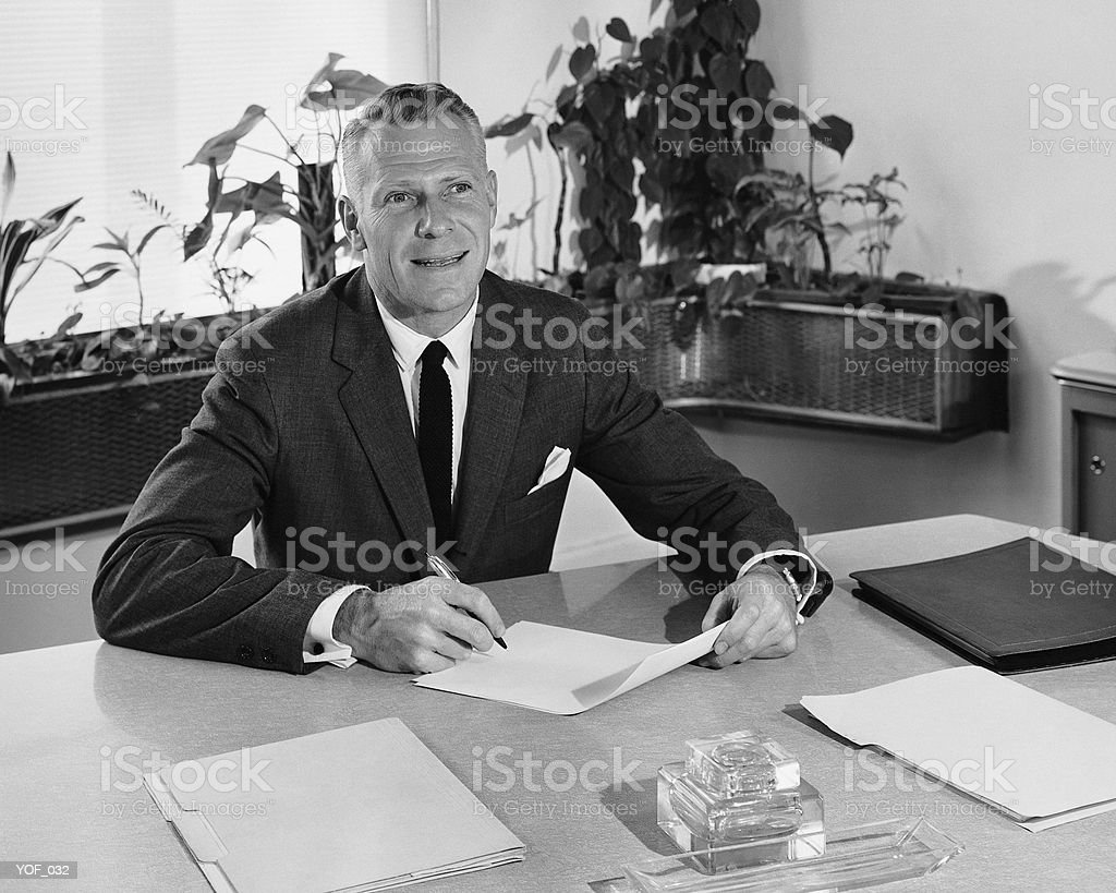 Man sitting at desk, holding paper and pencil royalty free stockfoto