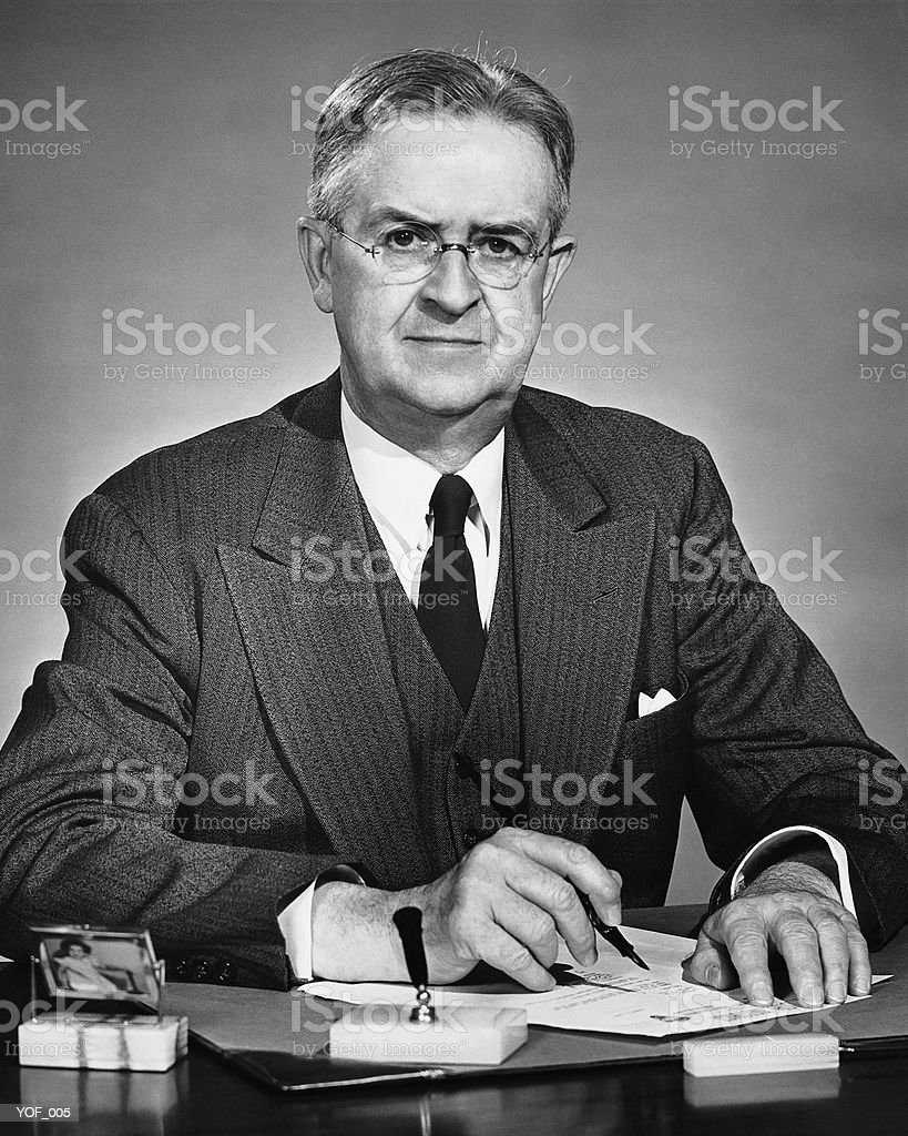 Man sitting at desk, holding pen 免版稅 stock photo