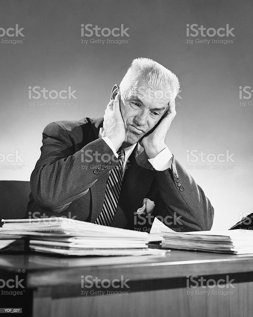 Man sitting at desk, leaning on elbows royalty free stockfoto