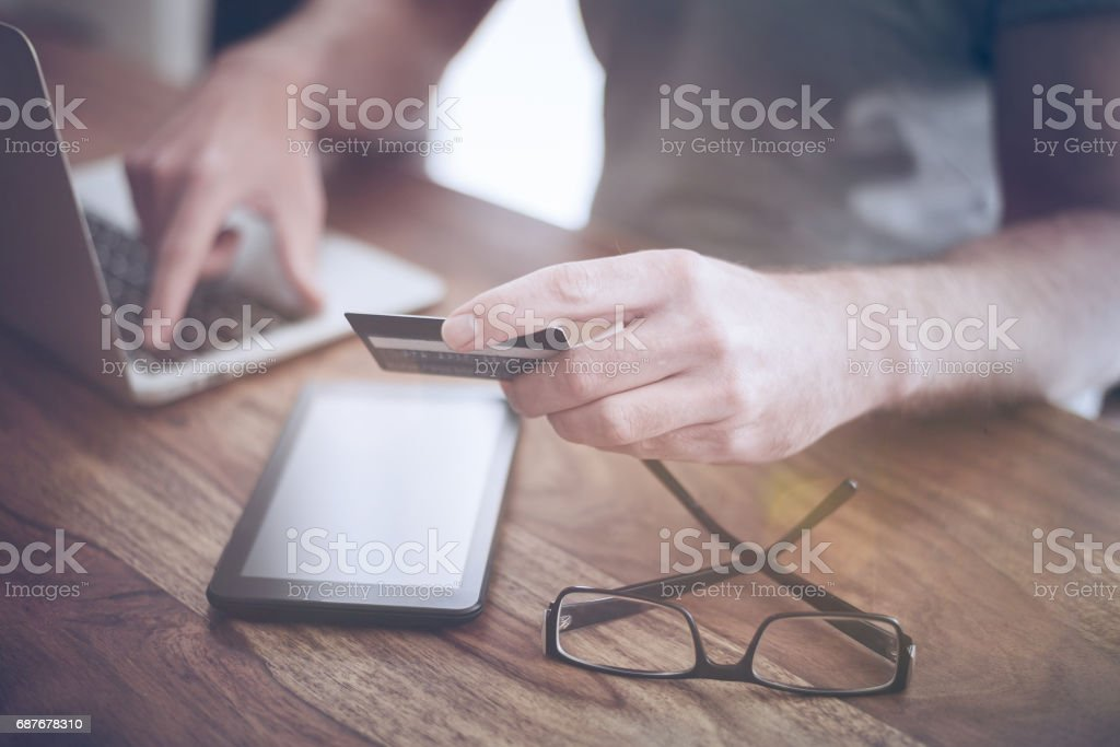 man sitting at rustic wood desk holding a credit card while typing on a laptop computer – Foto