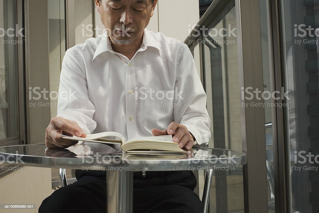 Man sitting at table on balcony reading book royalty-free stock photo