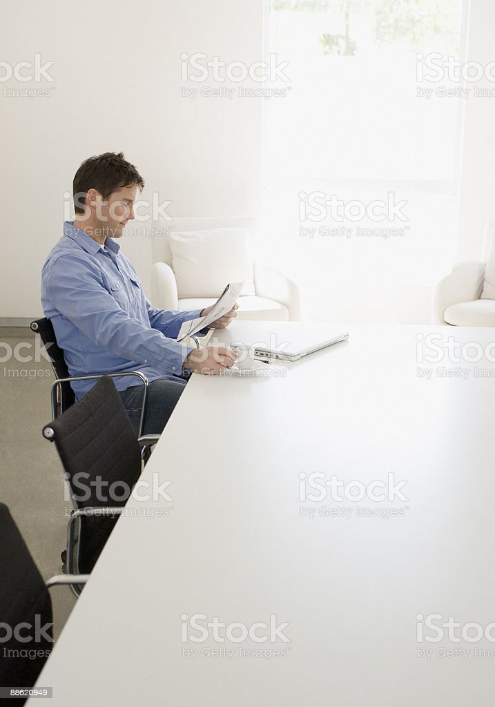 Man sitting at table with laptop and newspaper royalty-free stock photo