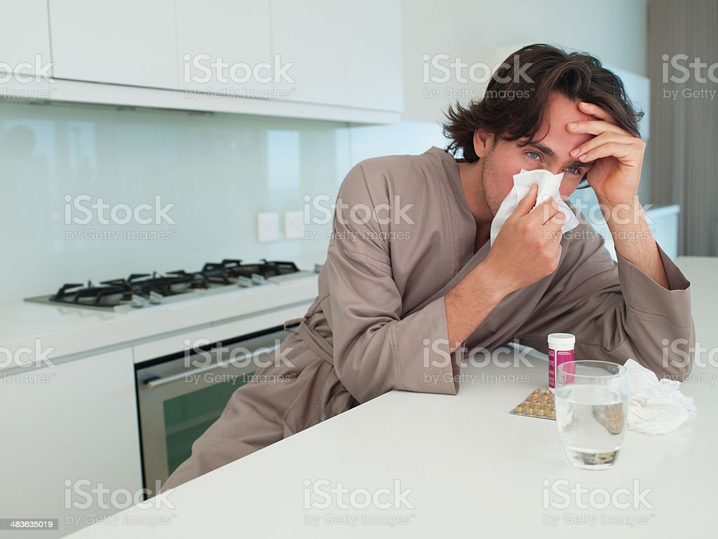 Man sitting at table with tissue blowing nose and holding head stock photo
