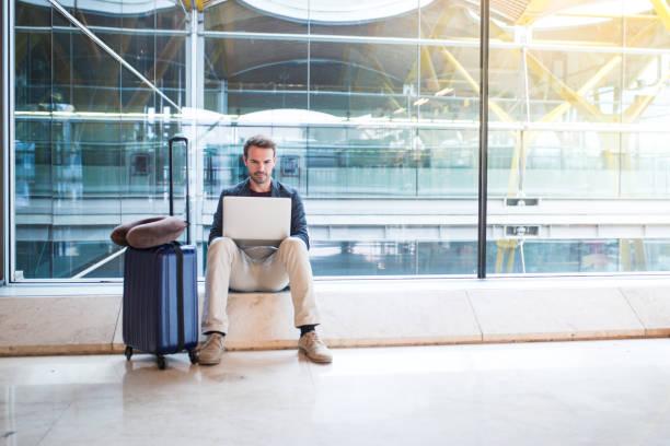 man zit op de luchthaven met behulp van de laptop en mobiele telefoon naast het venster - airport pickup stockfoto's en -beelden