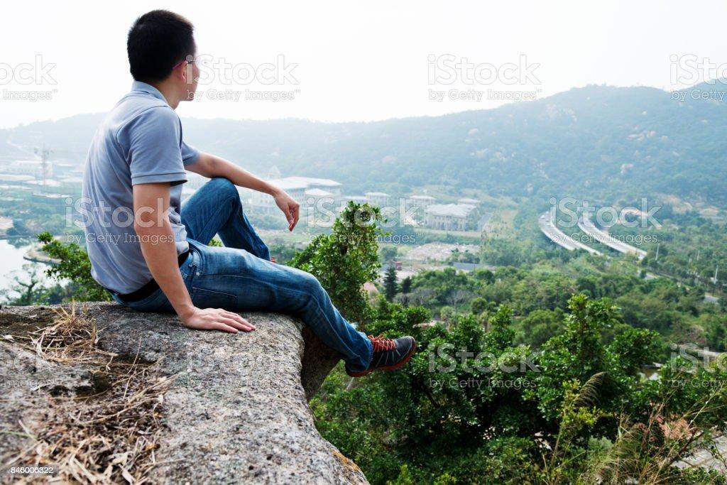 Mann sitzt am Rand einer Klippe Lizenzfreies stock-foto