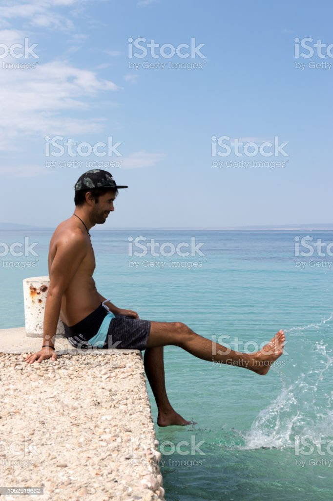 Man sitting at the end of the pier and splashing water stock photo