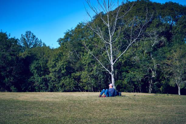 Homem sentado ao pé de uma árvore seca em um campo aberto para o budista templo Chagdud Gonpa Khadro Ling de Três Coroas. - foto de acervo