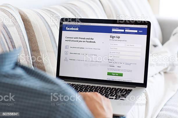 Uomo Seduto A Retina Macbook Con Sito Di Facebook - Fotografie stock e altre immagini di Adulto